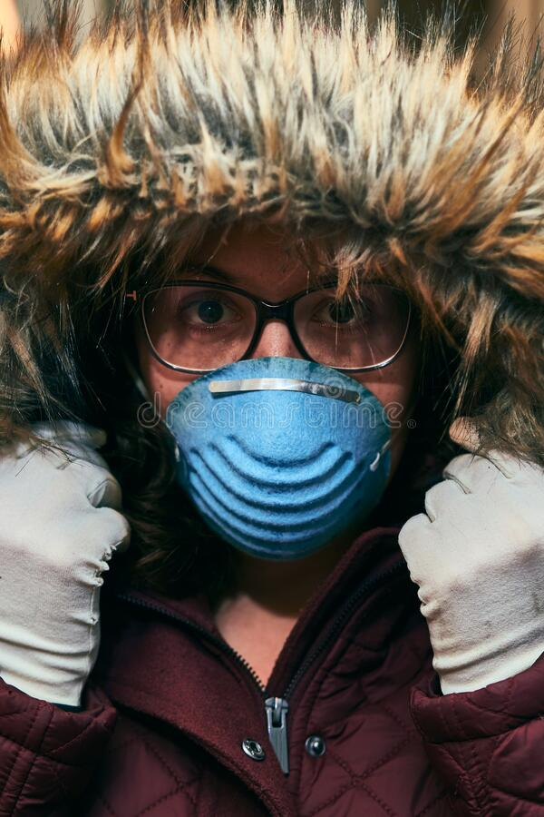 Girl wearing a hood, gloves and mask for coronavirus protection. Portrait of a girl wearing a hood, glasses, gloves and a mask for protection against coronavirus stock photos