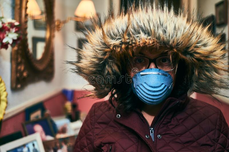 Girl wearing a hood and mask for coronavirus protection. Portrait of a girl wearing a hood, glasses and a mask for protection against coronavirus royalty free stock photos
