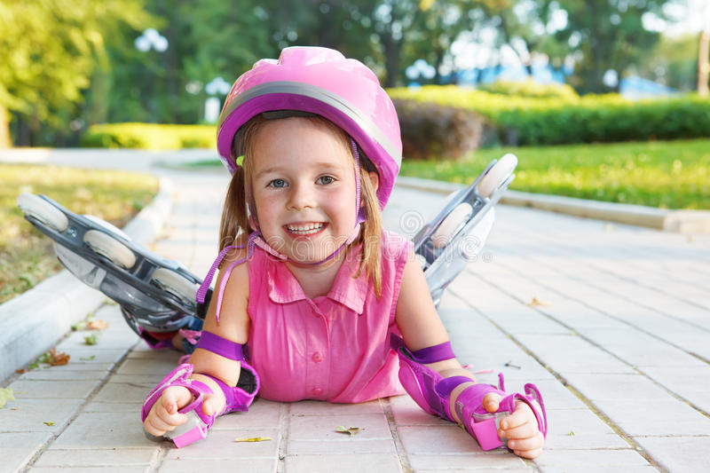 Girl wearing inline roller skates. Cheerful preschool girl wearing inline roller skates and protective equipment royalty free stock photos