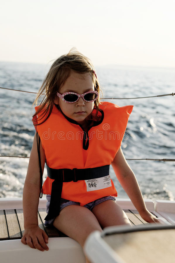 Girl wearing life jacket. Young girl sat on side of boat at sea wearing orange life jacket stock photo