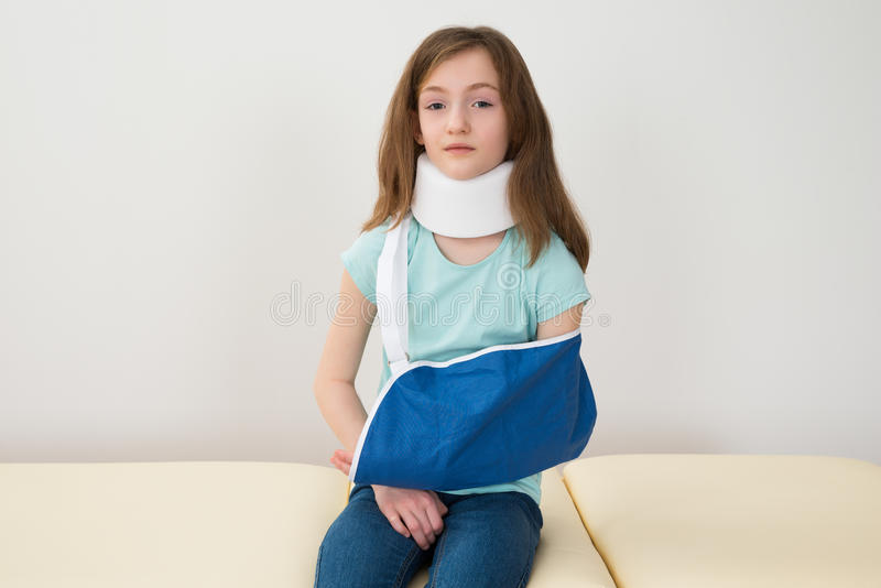 Girl Wearing Neck Brace And Arm Sling. Portrait Of Girl Wearing Neck Brace And Arm Sling royalty free stock photos