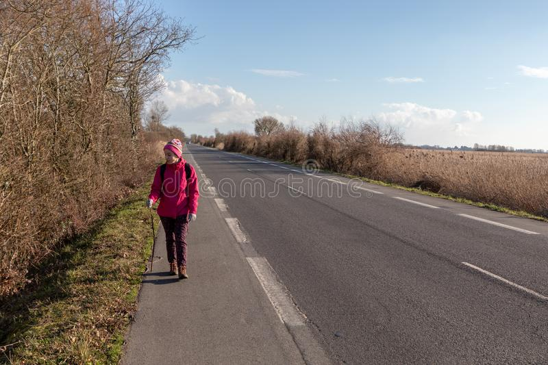 Girl walking on the shoulder of a road royalty free stock photos