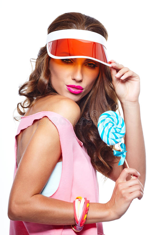 Girl wearing plastic cap holding lollipop. Glamourous girl wearing plastic cap holding lollipop stock photography