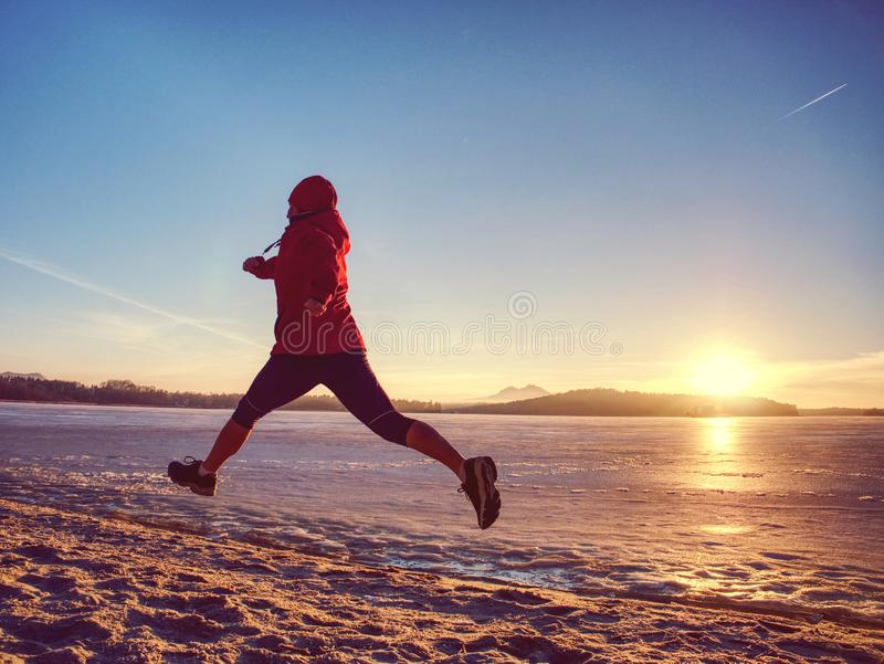 Girl wearing red black sportswear and running on snow stock photo