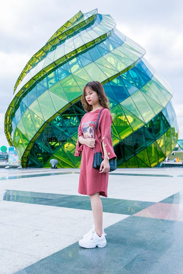 Girl Wearing Red Long-sleeved Dress and White Low-top Shoes Standing Near Green Glass Structure stock images