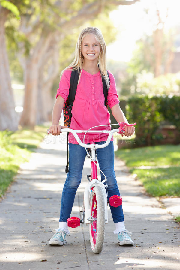 Girl Wearing Rucksack Cycling To School. Smiling stock photography