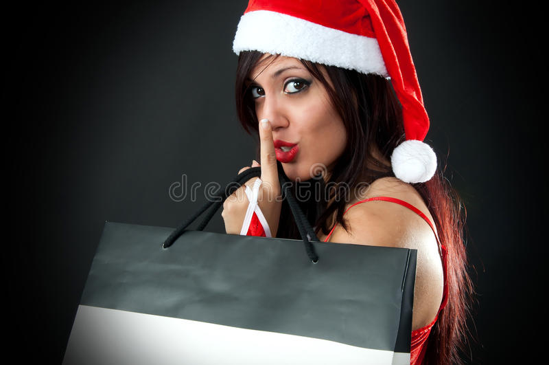 Girl wearing santa claus clothes with shopping bag. Portrait of Beautiful girl wearing santa claus clothes with shopping bag say sssshhhhh royalty free stock photos