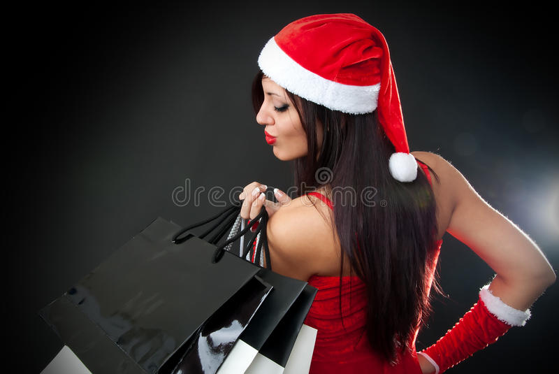 Girl wearing santa claus clothes with shopping bag. Portrait of Beautiful girl wearing santa claus clothes with shopping bags stock photography