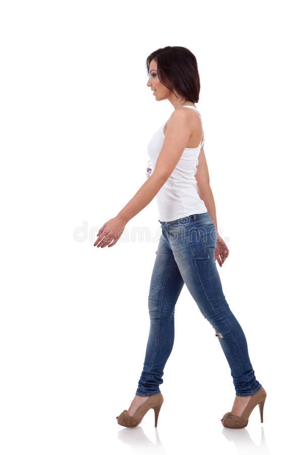 Girl wearing shirt and jeans walking royalty free stock photography