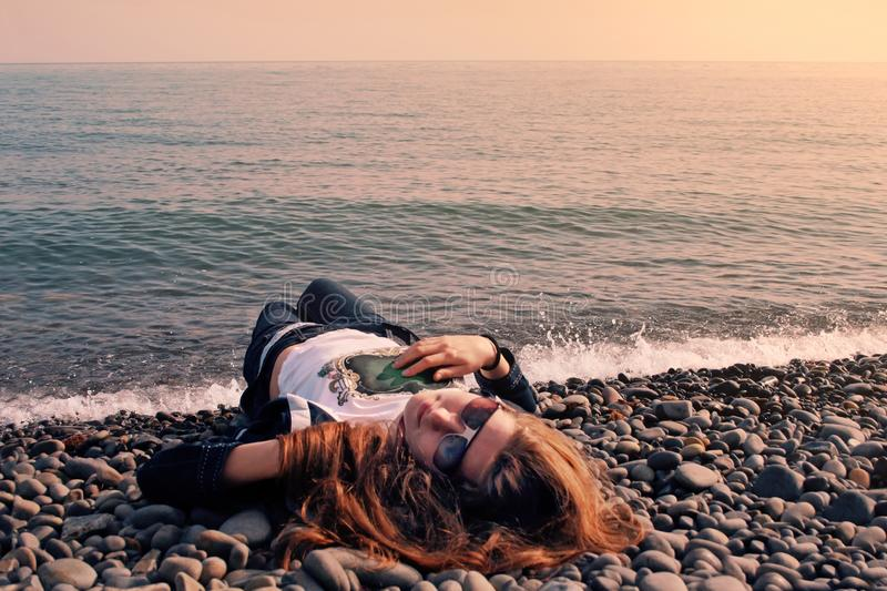 A girl wearing sunglasses lies on a pebble beach stock photo