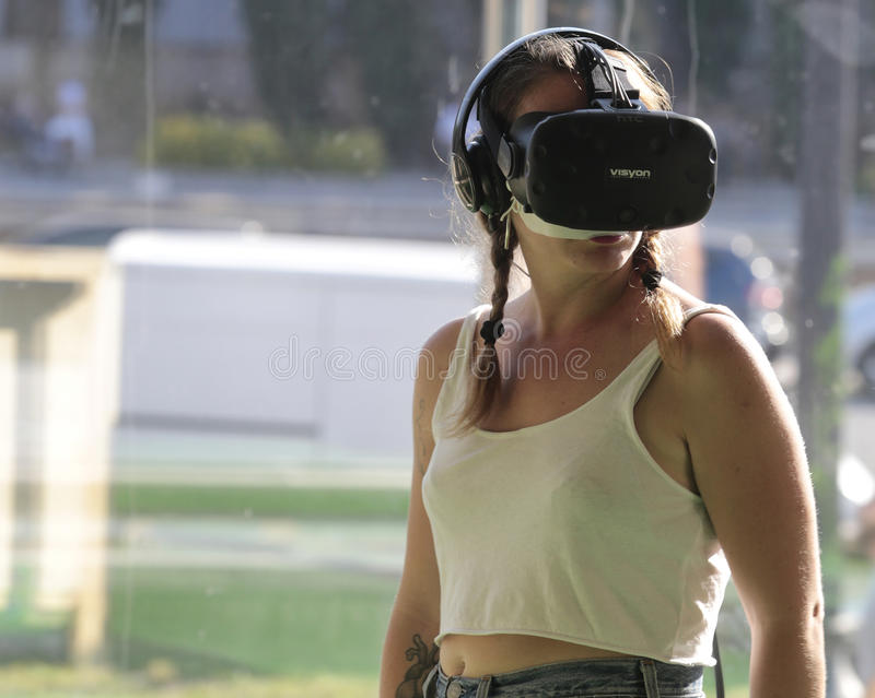 Girl wearing Vr devices. A girl gestures while wearing virtual reality VR equipment during Sonar advanced technology music and arts festival in barcelona stock image