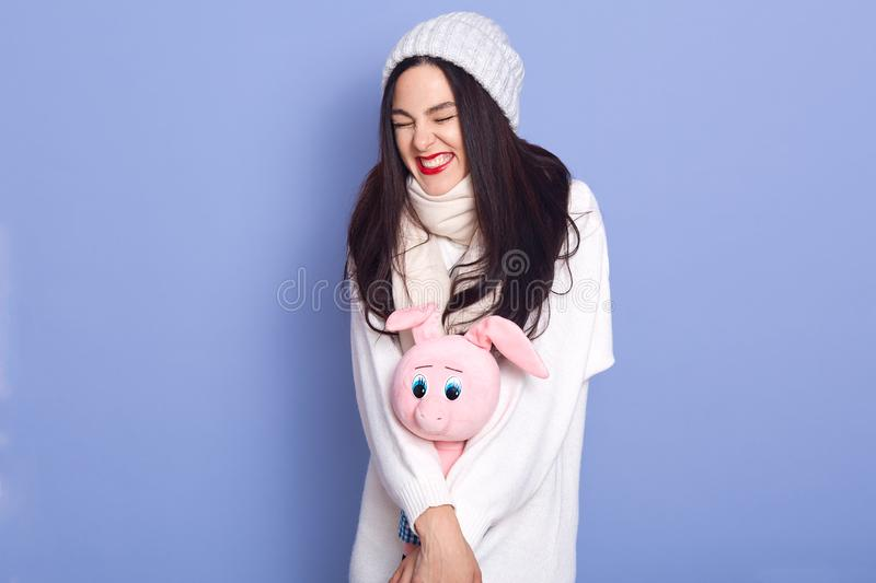 Girl wearing white cap, sweater and scarf holding rose toy pig, ready to celebrate new year and Christmas, posing with closed eyes royalty free stock image