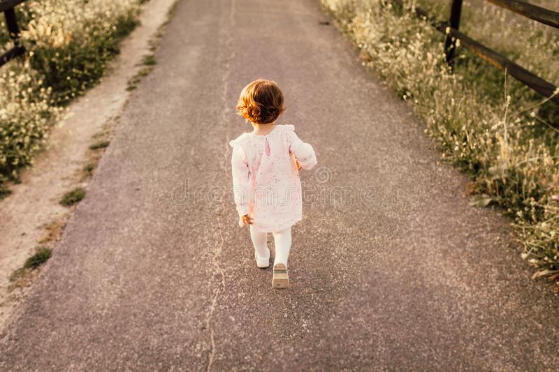 Girl Wearing White Clothes Walking on Pavement Road stock image
