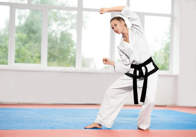 Girl wearing in white kimono with black belt practicing martial arts. stock photos