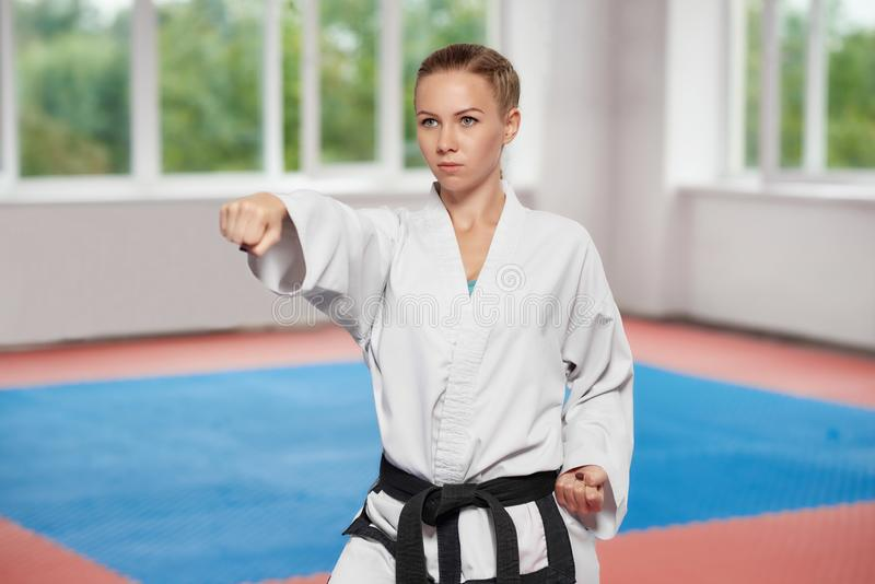 Girl wearing in white kimono with black belt standing in karate pose. royalty free stock photos
