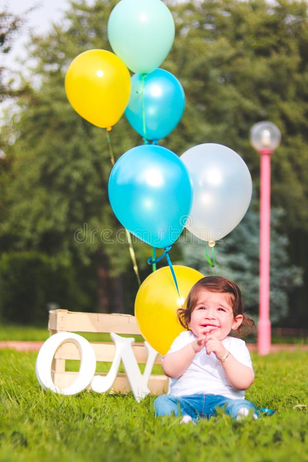 Girl Wearing White Shirt Near Teal, White, and Yellow Ballons stock photo