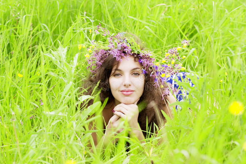 Girl wearing a wreath of wild flowers in the field. The image of a girl wearing a wreath of wild flowers in the field royalty free stock photo