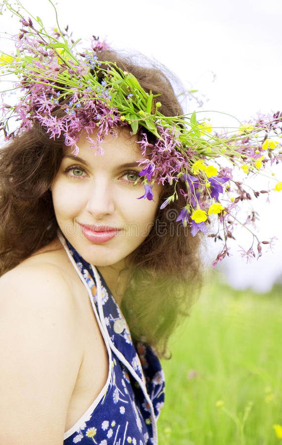 Girl wearing a wreath of wild flowers in the field. The image of a girl wearing a wreath of wild flowers in the field stock photo