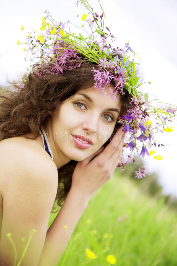 Girl wearing a wreath of wild flowers in the field. The image of a girl wearing a wreath of wild flowers in the field stock images