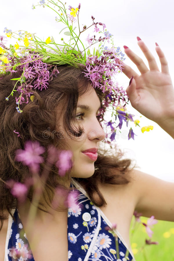 Girl wearing a wreath of wild flowers in the field. The image of a girl wearing a wreath of wild flowers in the field royalty free stock photography