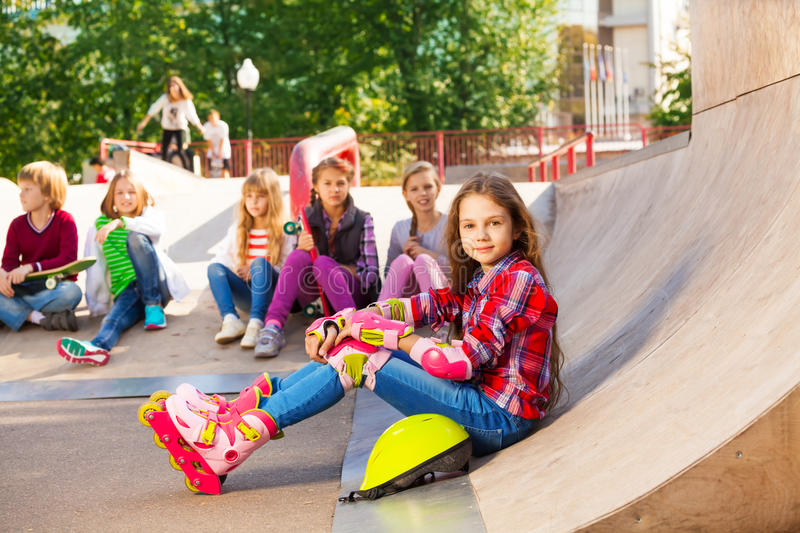 Download Girl Wears In-line Skates Sits In Front With Mates Stock Image - Image: 46654903