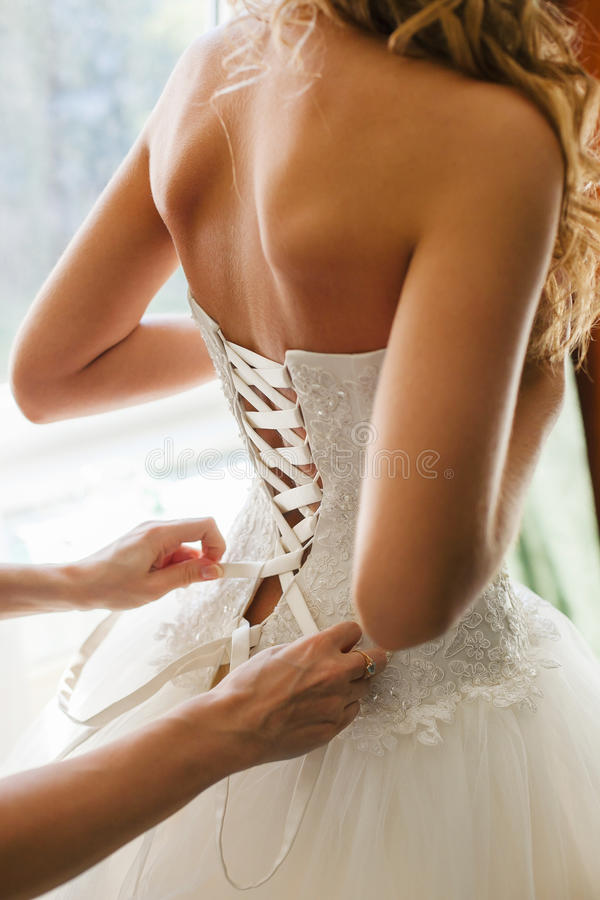 Girl in Wedding Dress Back View. Bride Wear White. Girl in wedding dress back view. Bride wearing white dress, person helps her to lace up the gown. Luxury stock image
