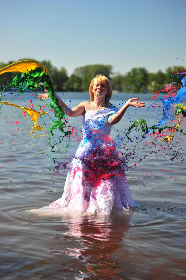 The girl in a wedding dress poured by a paint. The girl in a wedding dress standing in water poured by a paint royalty free stock photos