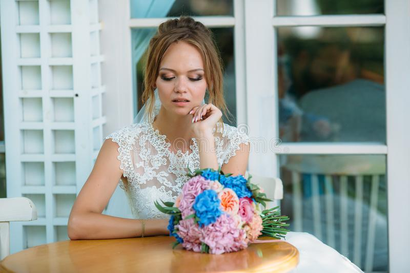 The girl in the wedding dress sits at the table alone and looks upset. The bride looks sadly at a bouquet of flowers. The girl in the wedding dress sits at the royalty free stock photography
