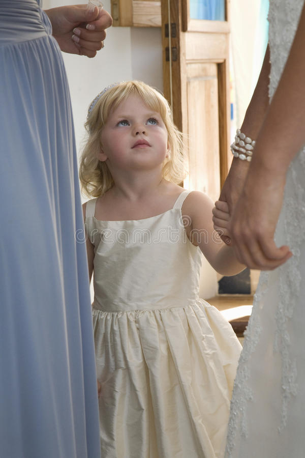 Girl At Wedding Reception. Little girl with two midsection woman at wedding reception royalty free stock image