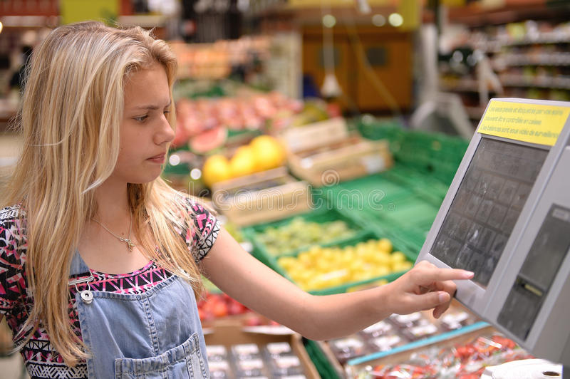 Girl weighing goods in shop. Blond girl weighing goods in shop with electronic touchscreen stock photo