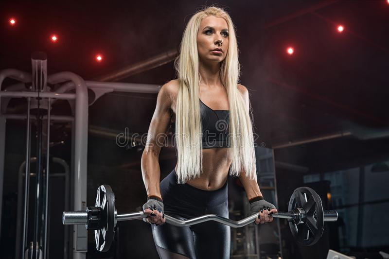 Young beautiful girl athlete bodybuilder at the gym doing exercises for the biceps using the barbell, in beautiful sportswear. Pe stock photography