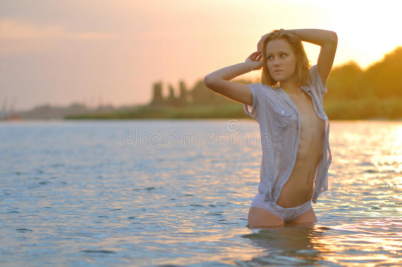 The girl in a wet shirt stand in the river. The beautiful girl in a wet shirt at sunset stock image