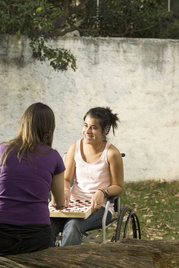Girl in Wheelchair. Young girl in wheelchair playing cards in with another girl. Vertically framed photo royalty free stock photo