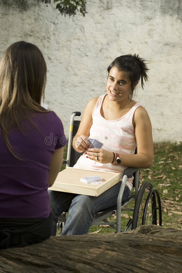 Girl in Wheelchair. Young girl in wheelchair playing cards in with another girl. Vertically framed photo stock image