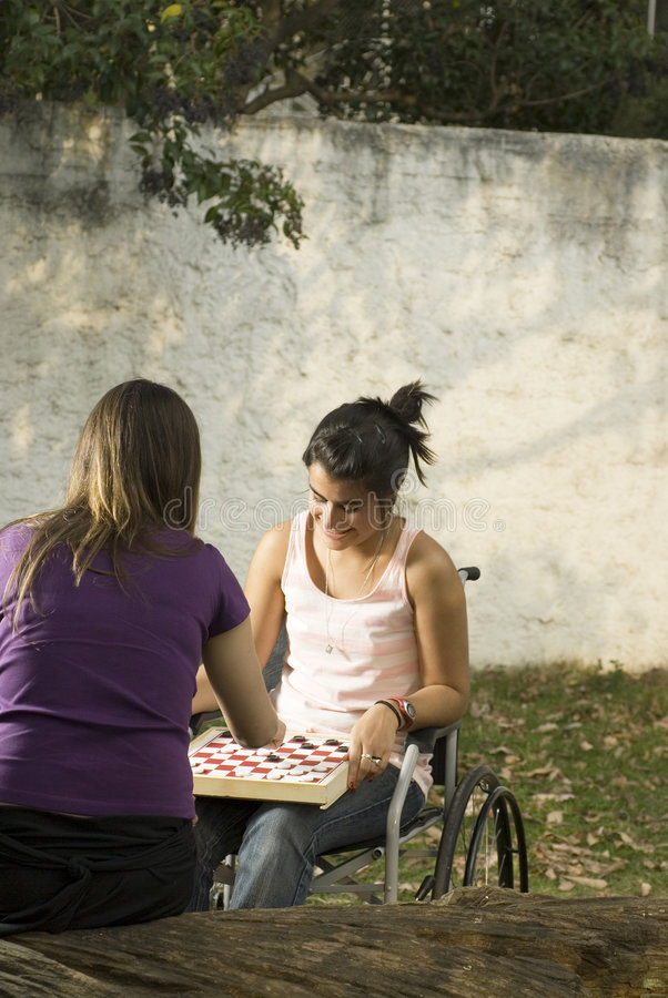 Girl in Wheelchair - Vertical. Young girl in wheelchair playing cards in with another girl. Vertically framed photo stock image