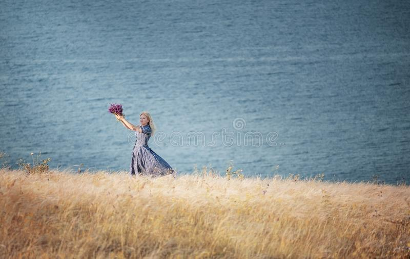 A girl whirling with a bouquet of wild flowers in her hands among the grass on a cliff by the sea. The atmosphere of happiness and royalty free stock images