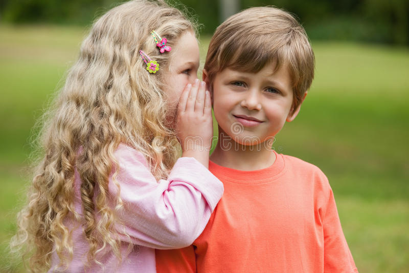 Girl whispering secret into boy's ear at park royalty free stock photos