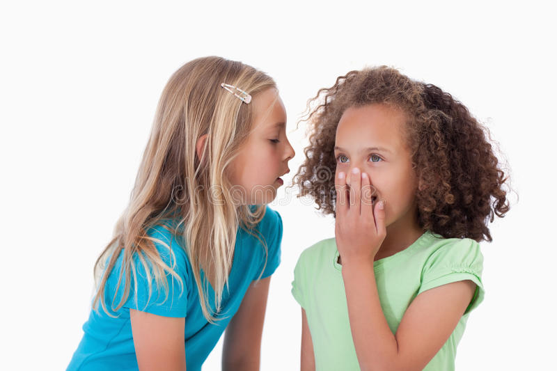 Girl whispering a secret to her friend