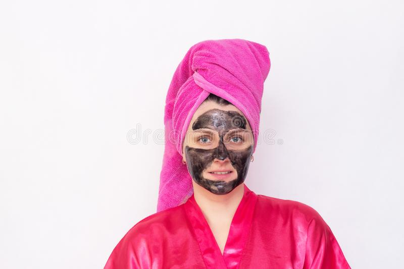 A girl on a white background with a black mask on her face against blackheads and black dots in a pink robe. And a towel on her head, copy space, procedure royalty free stock images