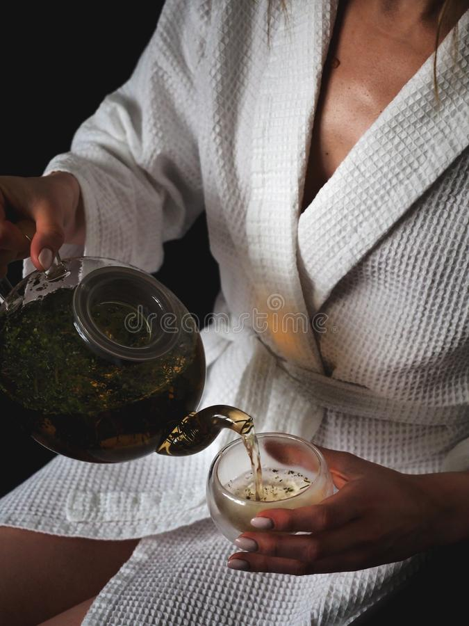 Girl in a white bath robe puring herbal tea in a transparent glass stock images