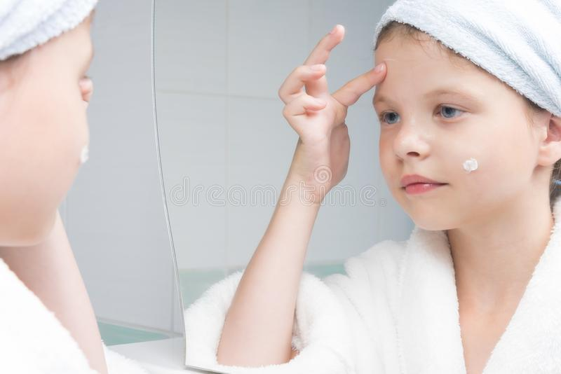Girl in a white bathrobe in the bathroom applies moisturizer to her face royalty free stock images