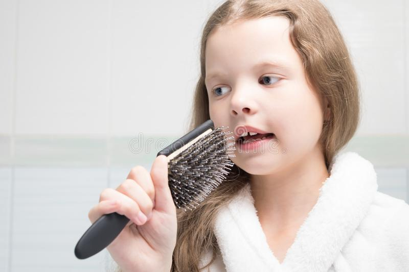 Girl in a white bathrobe in the bathroom holds a comb in her hand like a microphone stock images