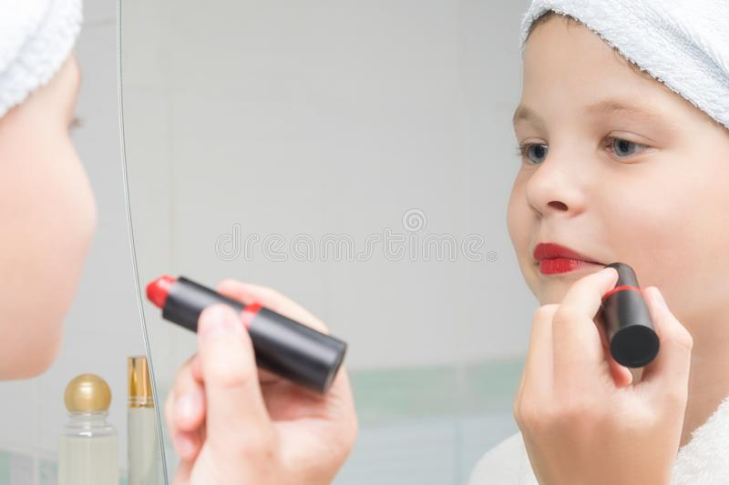 Girl in a white bathrobe in the bathroom paints her lips with red lipstick. Girl in a white bathrobe in the bathroom  paints her lips with red lipstick royalty free stock photography