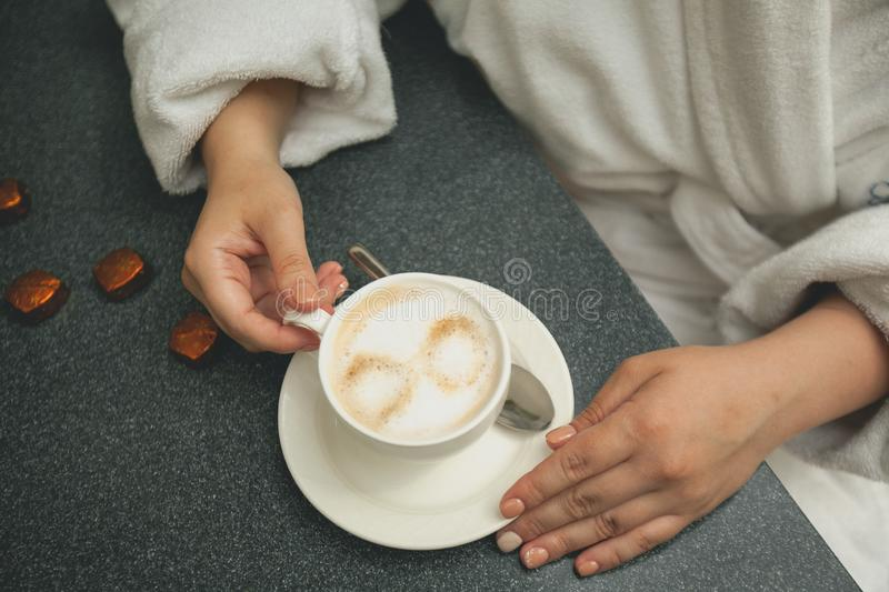 A girl in a white Bathrobe holding a Cup of coffee while relaxing at the Spa. Coffee with foam in a white mug on a saucer, next to royalty free stock photography