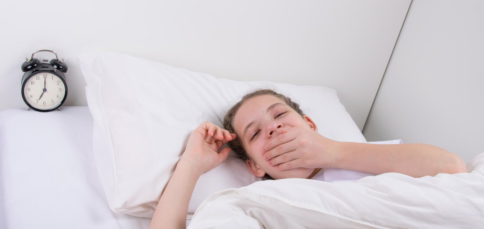 The girl, in a white bed, wakes up to the sound of an alarm clock stock photography