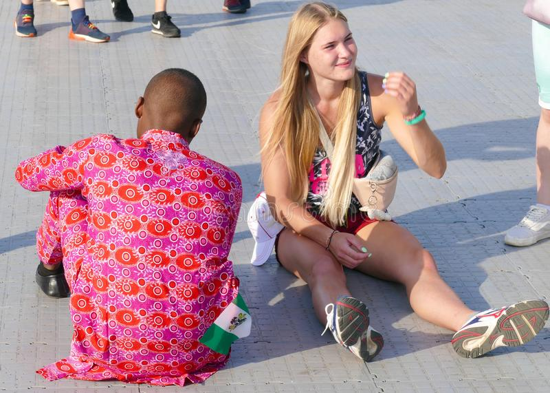 The girl is white and black is sitting on the street in the fan zone royalty free stock photo