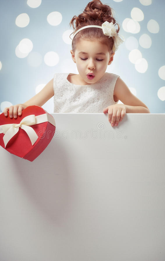 Girl with white blank poster. Sweet child girl with white blank poster banner. Happy little girl with gift box. Wedding, Valentine concept stock images