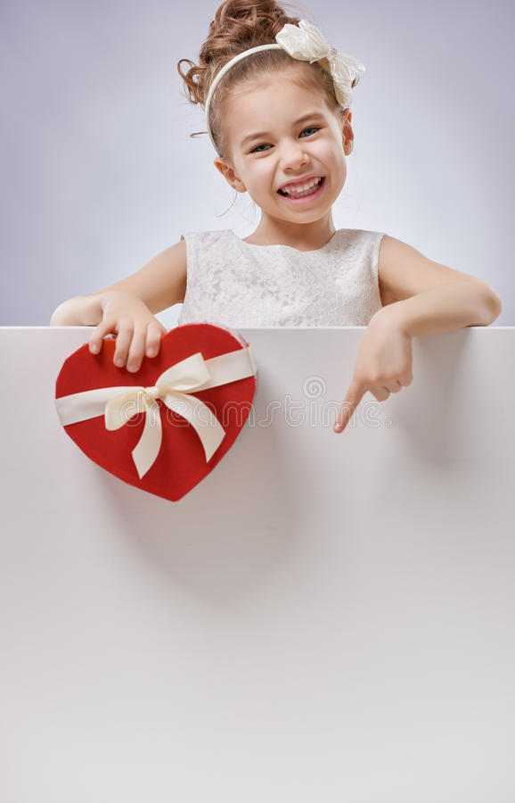 Girl with white blank poster. Sweet child girl with white blank poster banner. Happy little girl with gift box. Wedding, Valentine concept stock photos