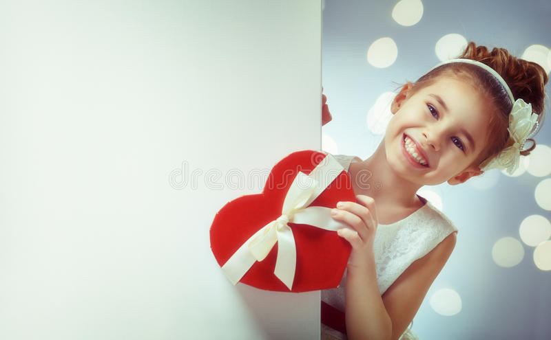 Girl with white blank poster. Sweet child girl with white blank poster banner. Happy little girl with gift box. Wedding, Valentine concept stock image