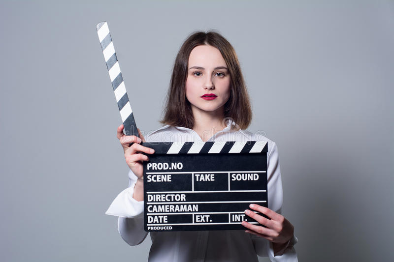 Girl in a white blouse with movie cracker. Girl in a white blouse with a movie cracker. Assistant director with a cracker on a gray background royalty free stock image